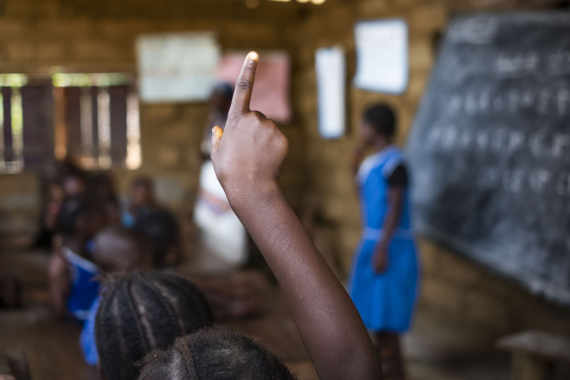 Young Girl Holding Up Hand In Classroom
