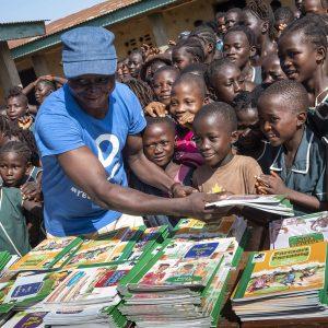 CODE Volunteer Handing Out Books To Children