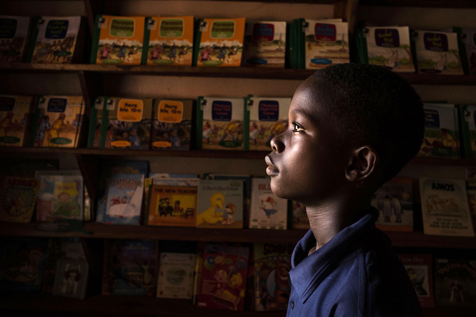 Child In Front Of Shelves Full Of Books