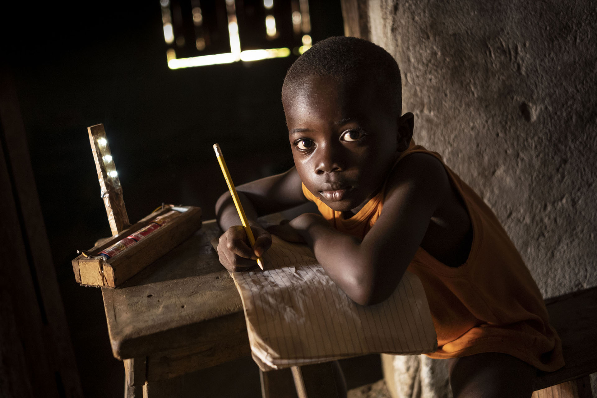 Young Child Writing In A Notebook In Class