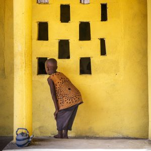 Child In Front Of Bright Yellow Wall Looking Through Square Windows